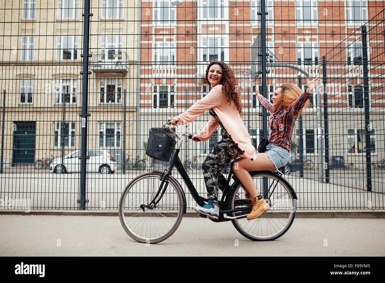 Porträt von zwei glücklichen jungen Frauen genießen Radtour auf Stadtstraße. Freundinnen auf Stockbild