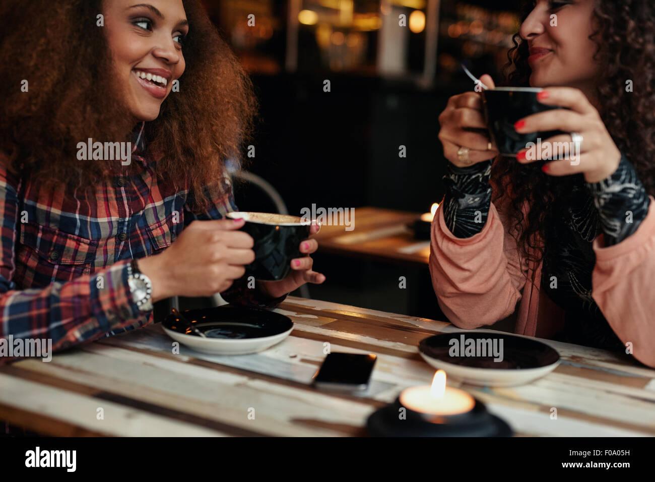 Schuss von einem jungen Freunden in einem Café beschnitten. Junge Frauen im Café sitzen am Tisch Kaffee Stockbild
