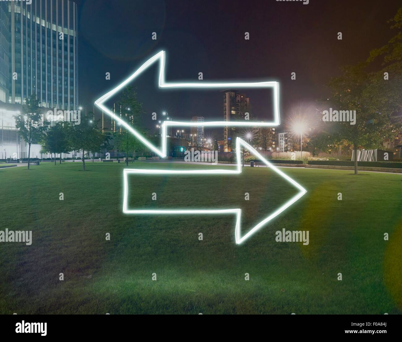 Glühende Richtungspfeile zeigen entgegengesetzte Richtungen in der Nacht, London, UK Stockbild