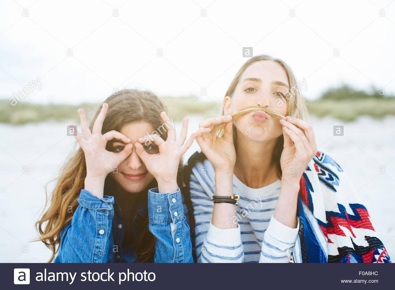 Porträt von zwei jungen Freundinnen machen Schnurrbart und brillentragende Gesichter am Strand Stockbild
