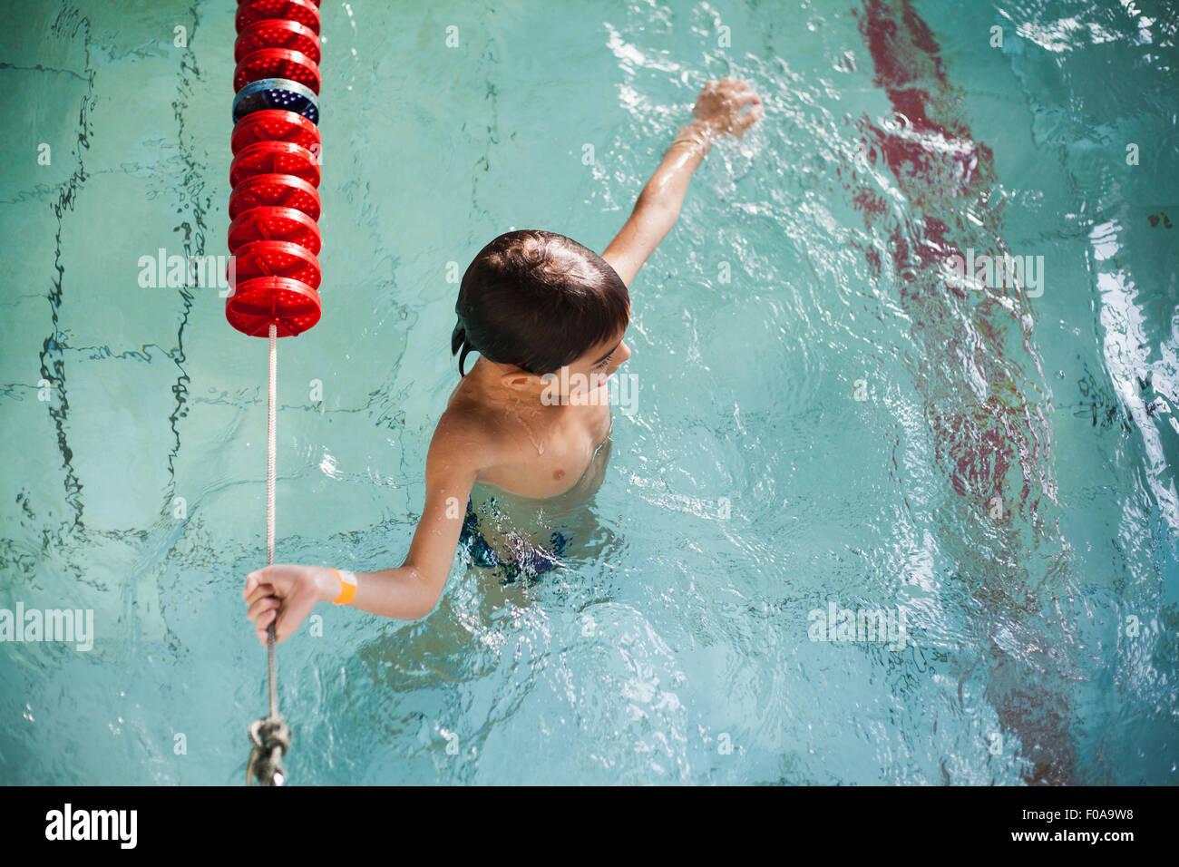 Erhöhte Ansicht des jungen festhalten Seil im Schwimmbad Stockbild