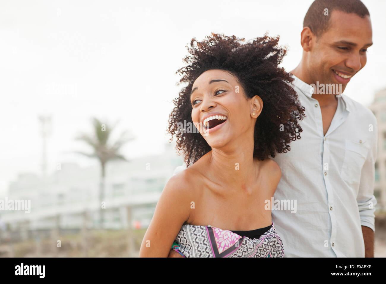 Junge Frau lachend mit Freund beim Spaziergang am Strand, Rio De Janeiro, Brasilien Stockbild
