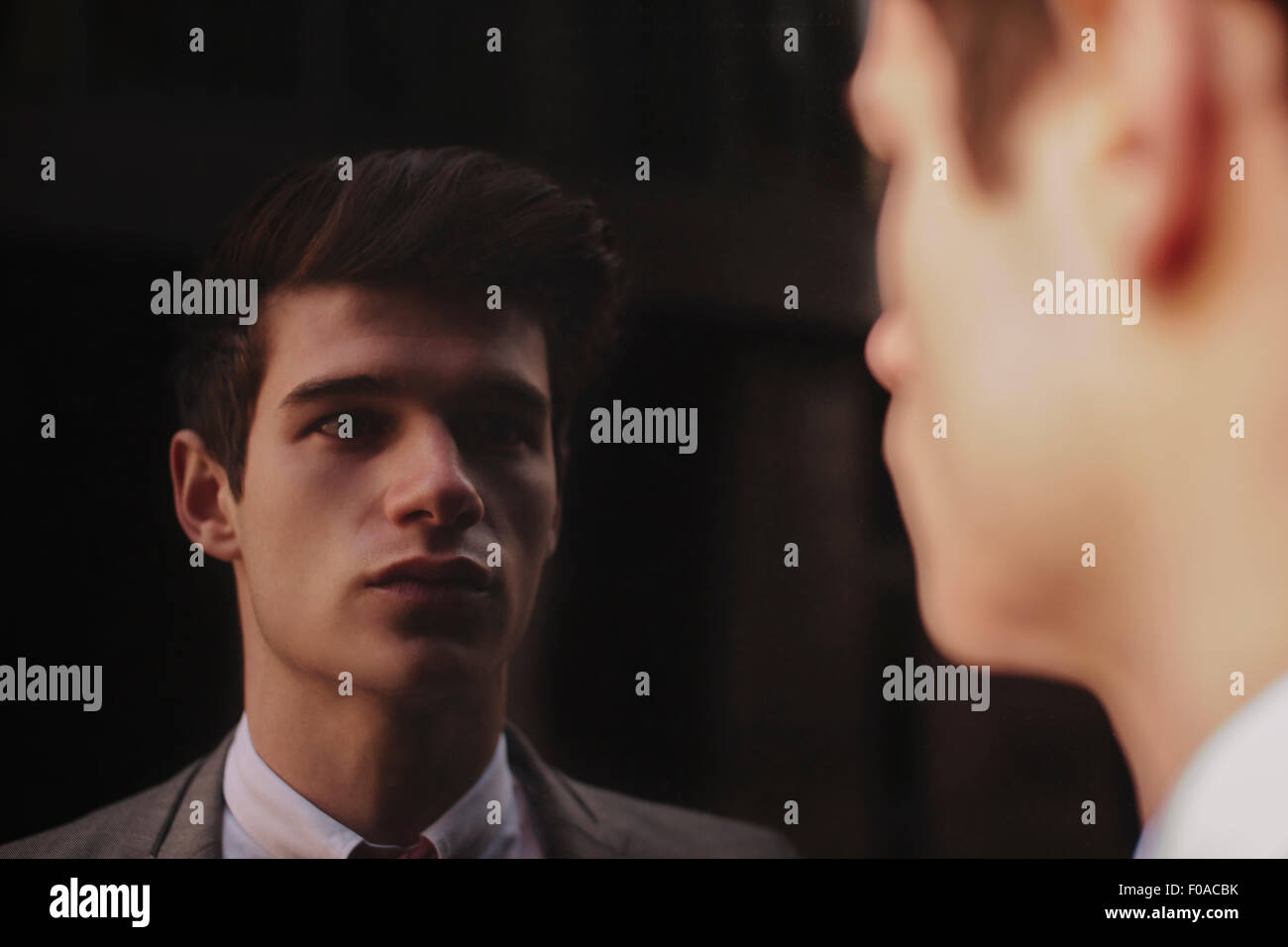 Spiegel-Porträt jungen Geschäftsmann starrte auf dunkel getönte Fenster Stockbild