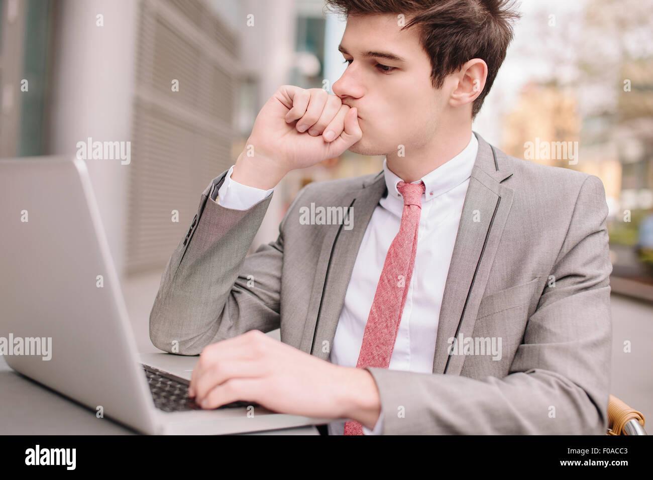 Besorgt junge Stadt Geschäftsmann mit Laptop im Straßencafé Stockbild