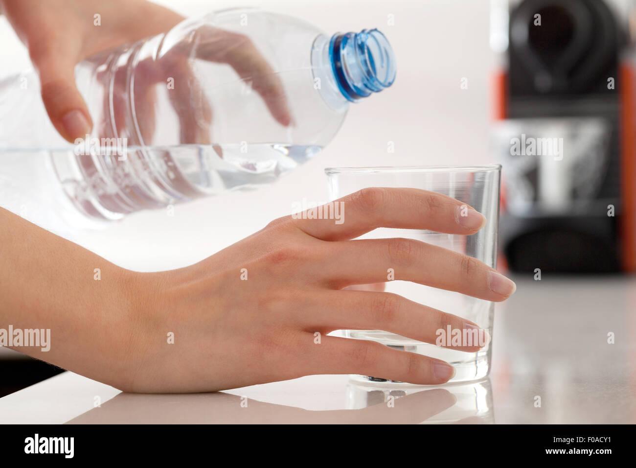 Weibliche Hände gießt Wasser in Flaschen in Glas Stockbild