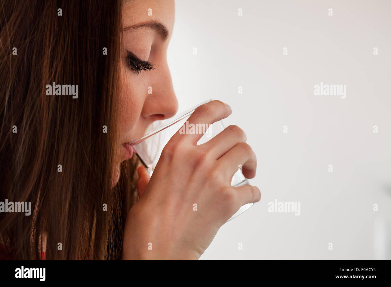 Junge Frau trinken Wasser aus Glas Stockbild