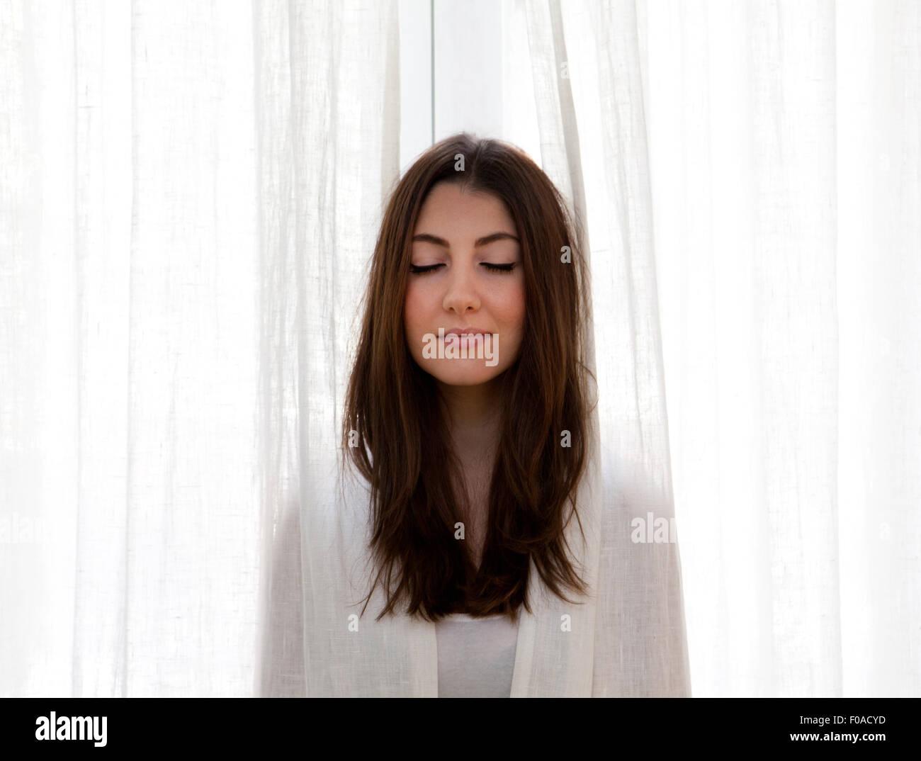 Junge Frau Stossen-Kopf aus Vorhängen, Augen geschlossen Stockbild
