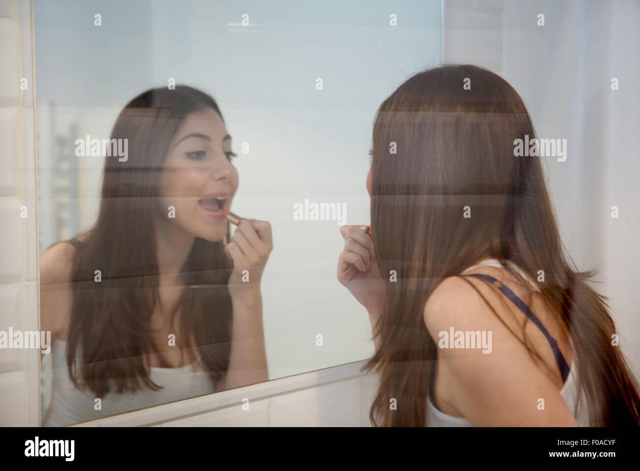 Junge Frau Anwendung machen sich im Spiegel Stockbild