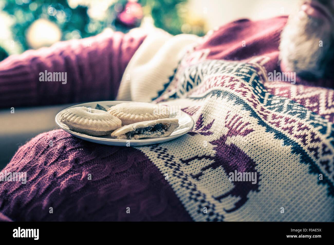 Mann mit Pullover mit Mince Pies schlafend auf Brust Stockbild