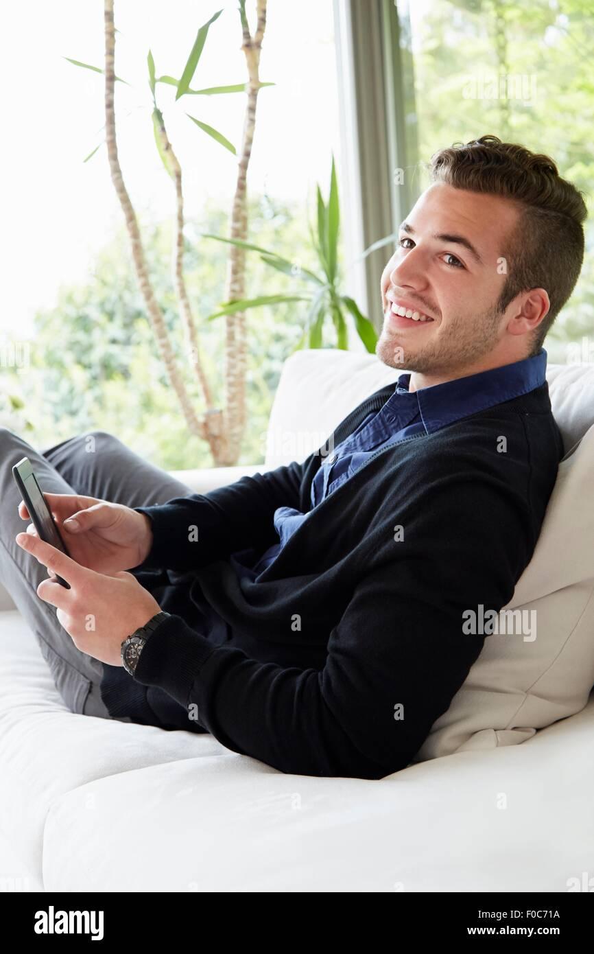 Porträt des Mannes entspannen Sie sich auf Sofa mit Füßen auf digitalen Lesens Haltevorrichtung Stockbild