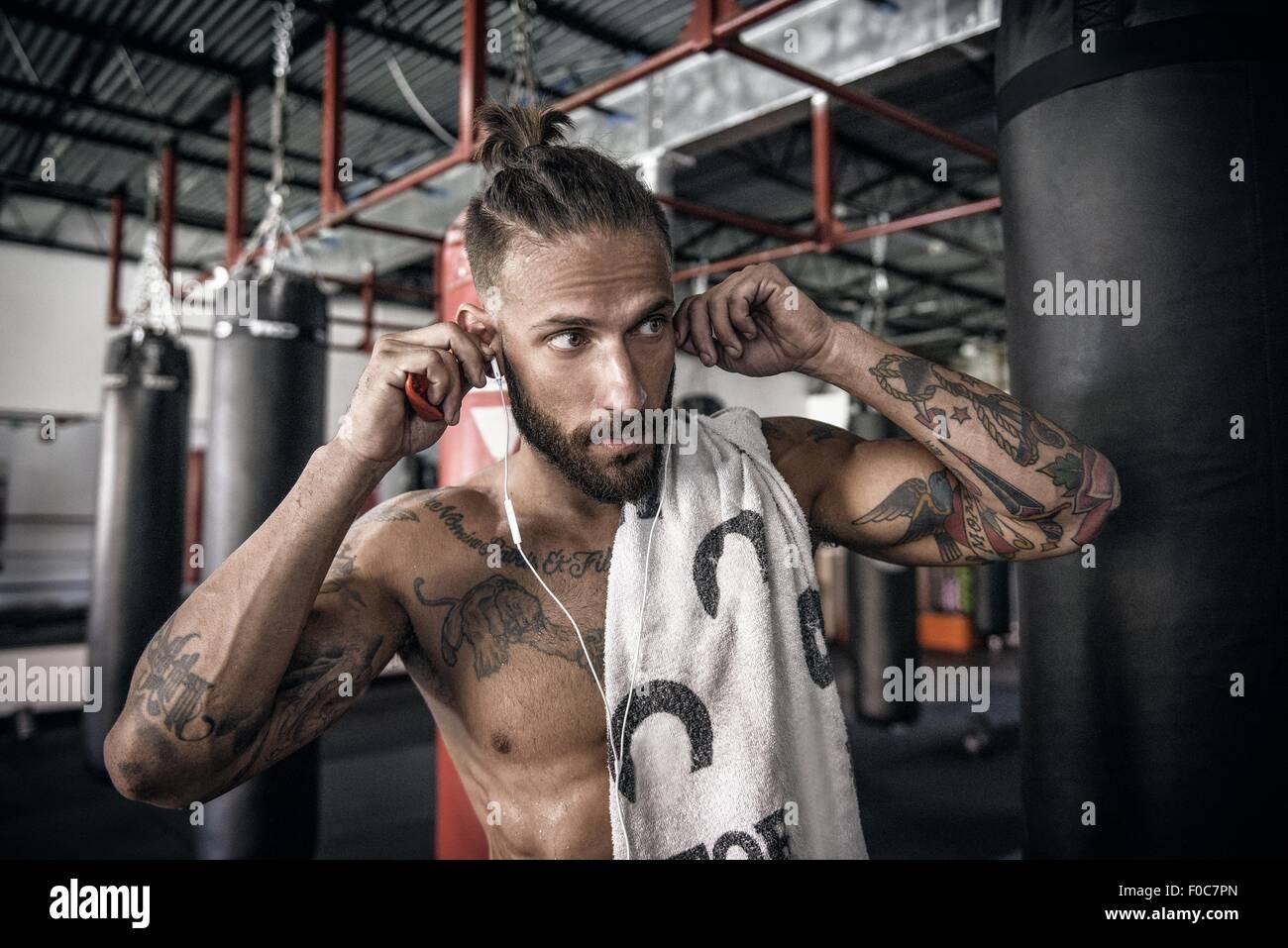 Männlicher Boxer setzen Kopfhörer in Turnhalle Stockbild