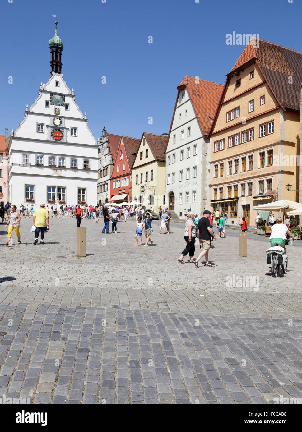 Touristen zu Fuß von typischen Gebäuden auf dem Marktplatz Marktplatz, Rothenburg Ob der Tauber, Franken, Stockbild