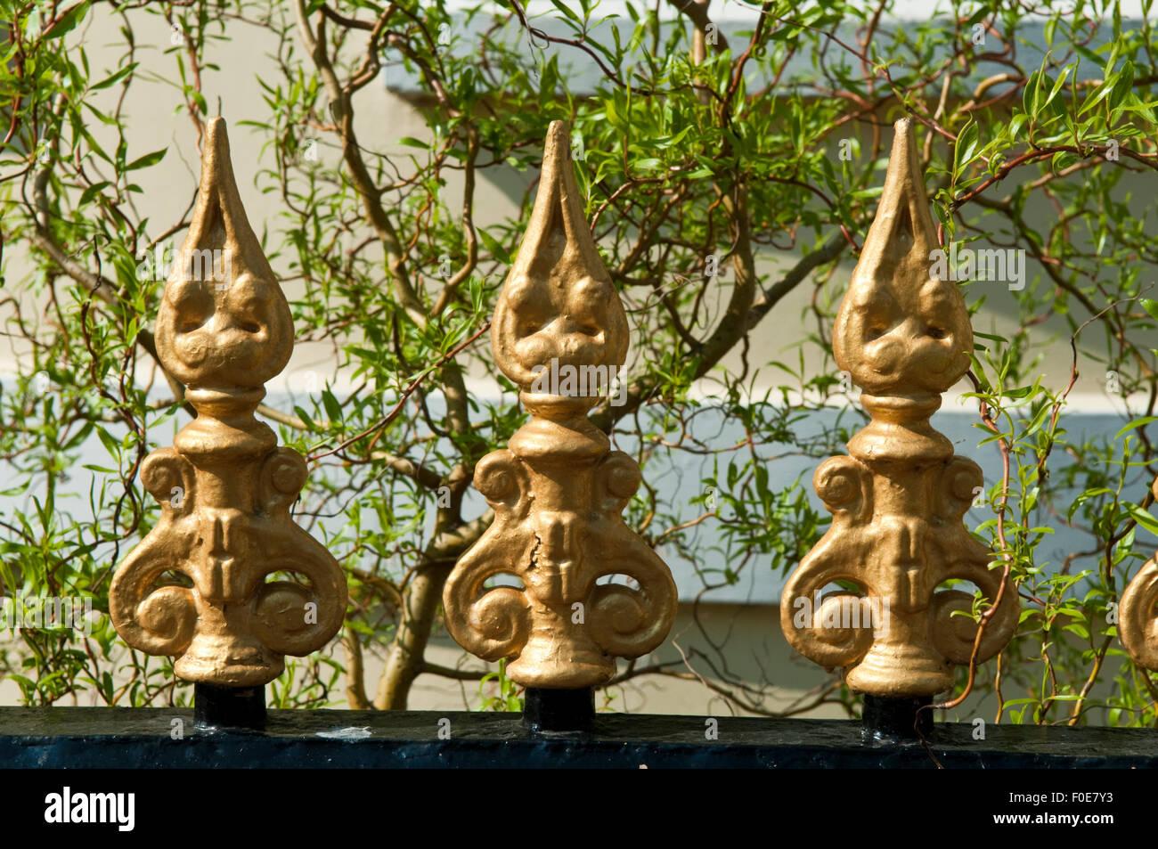 Drei dekorative Gold lackiert Metall-Spikes auf einem gusseisernen Zaun Geländer Stockbild