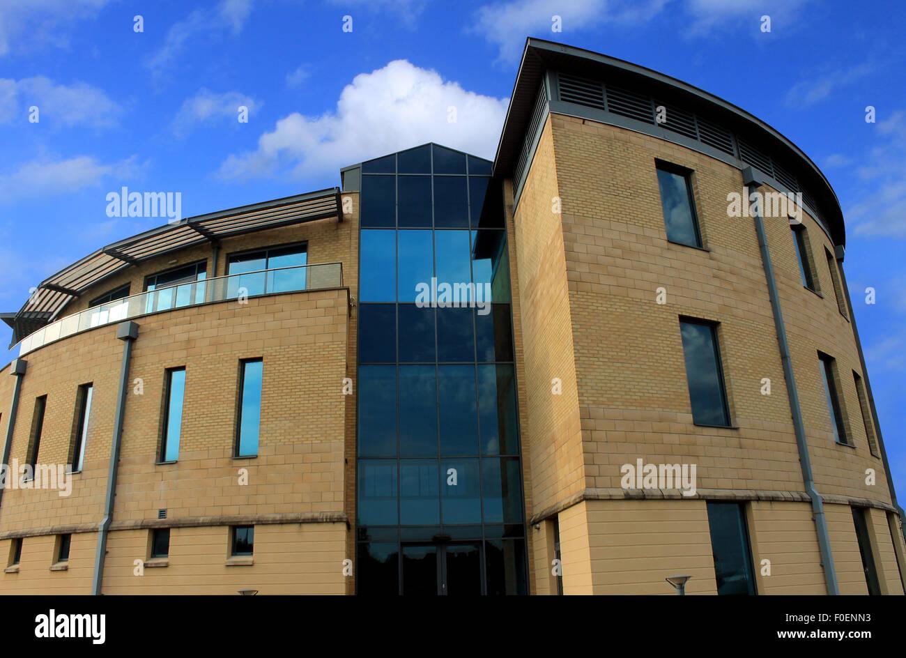 Außen ein neues, modernes Bürogebäude mit blauen Himmel und Wolken. Stockbild