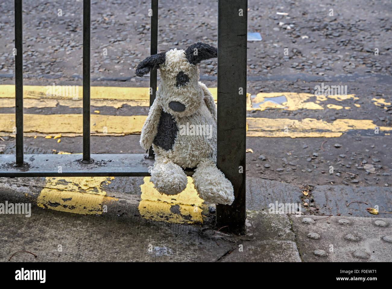 Ein Kind verloren Kuscheltier Hundesitting am Geländer, die darauf warten, gefunden werden. Stockbild
