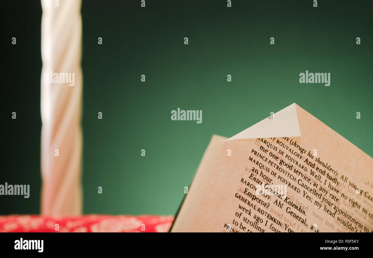 Buchseite auf aktuelle Seite markieren, unter Lampe Licht, faltbar links auf roten Sessel ruht, nach der Lektüre, Stockbild