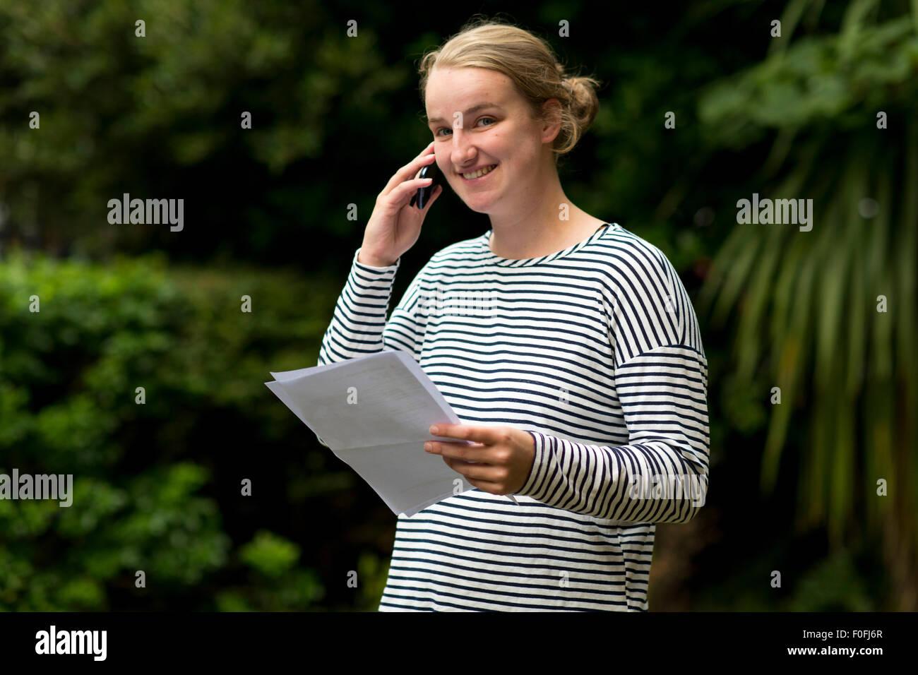 Eine blonde GCSE Studentin mit ihren Prüfungsergebnissen zufrieden. Stockbild