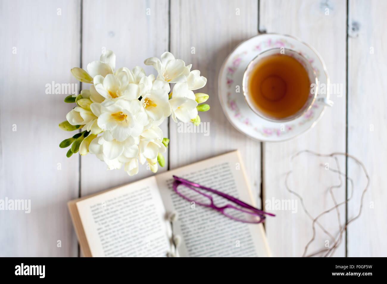 Nahaufnahme des weißen Freesien auf blauen Tischset mit unscharfen Vintage Teetasse und Untertasse im Hintergrund, Stockbild