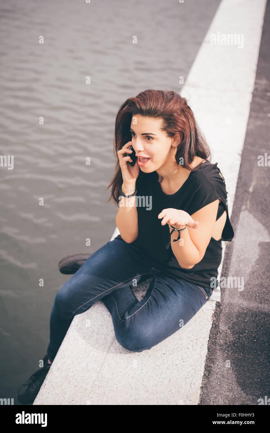 b12a0810be4e Junge schöne rötliche braune Haare kaukasische Mädchen sprechen Smartphone  sitzen auf einem Bürgersteig auf Navigli, mit Blick auf - Technologie,