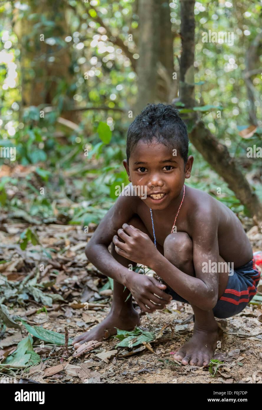 Kleiner Junge des Stammes Orang Asil grinsend, hocken auf dem Boden in den Dschungel, native, indigene Volk Stockbild