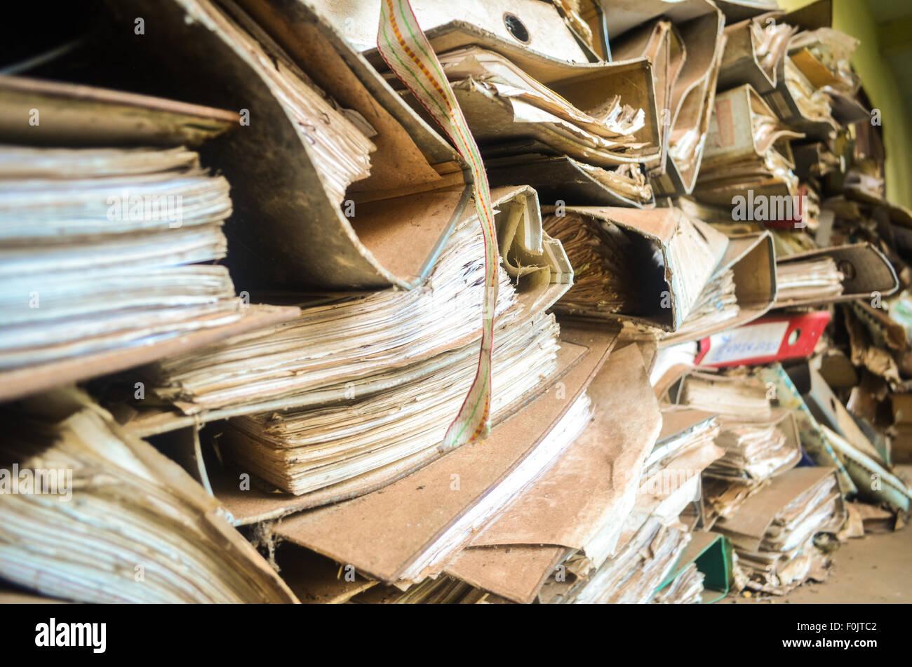 Alte gelbliche Dateien aufgeschichtet und mit Staub bedeckt Stockbild