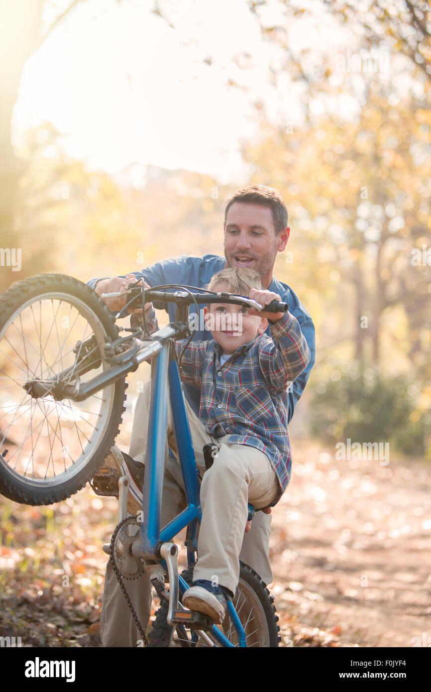 Vater Sohn beizubringen, wie man einen Wheelie im Wald zu tun Stockfoto