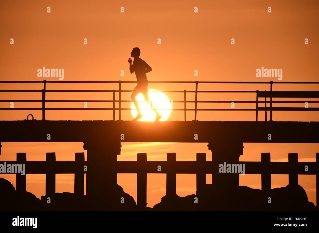 Aberystwyth, Wales, UK. 17. August 2015. UK-Wetter: Ein einsamer Mann joggt Silhouette bei Sonnenuntergang entlang Stockbild