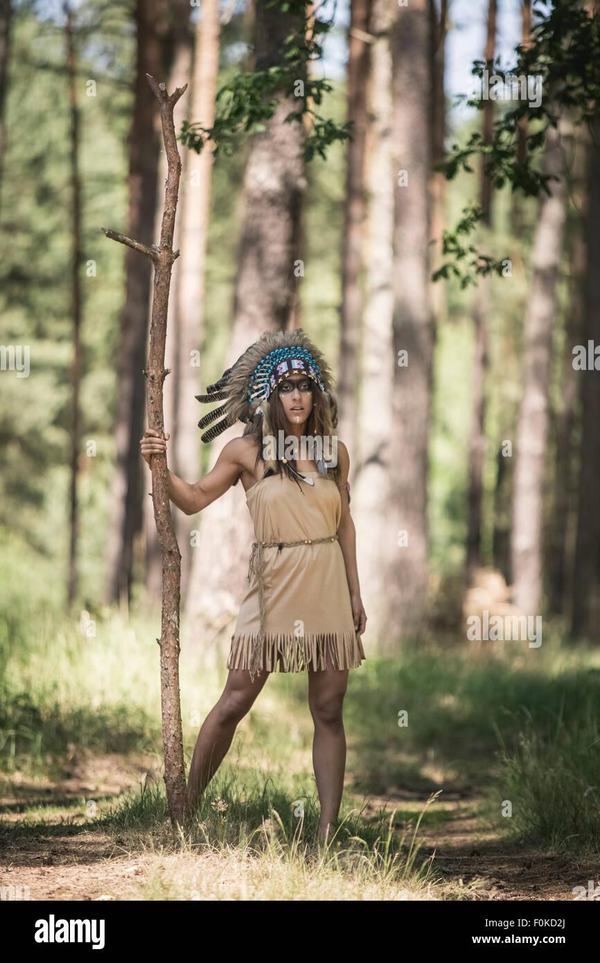 Junge Frau Maskerade als ein indischer steht im Wald Stockbild