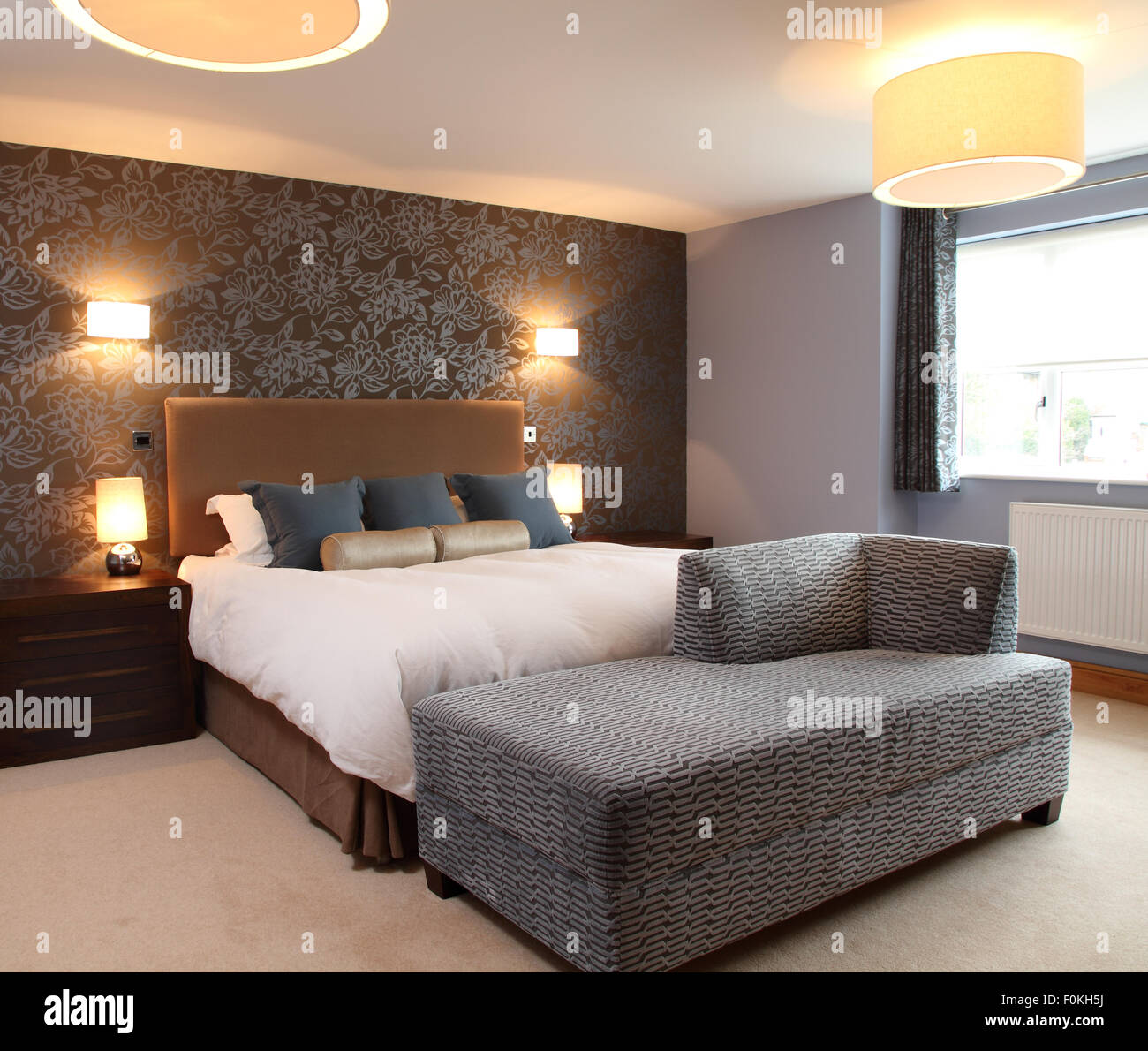 Moderne Schlafzimmer Mit Wandleuchten Und Tischleuchten Seite. Gepolsterte  Camel Farbige Kopfteil. Braune Tapete Mit Grauen Blume Design Wand