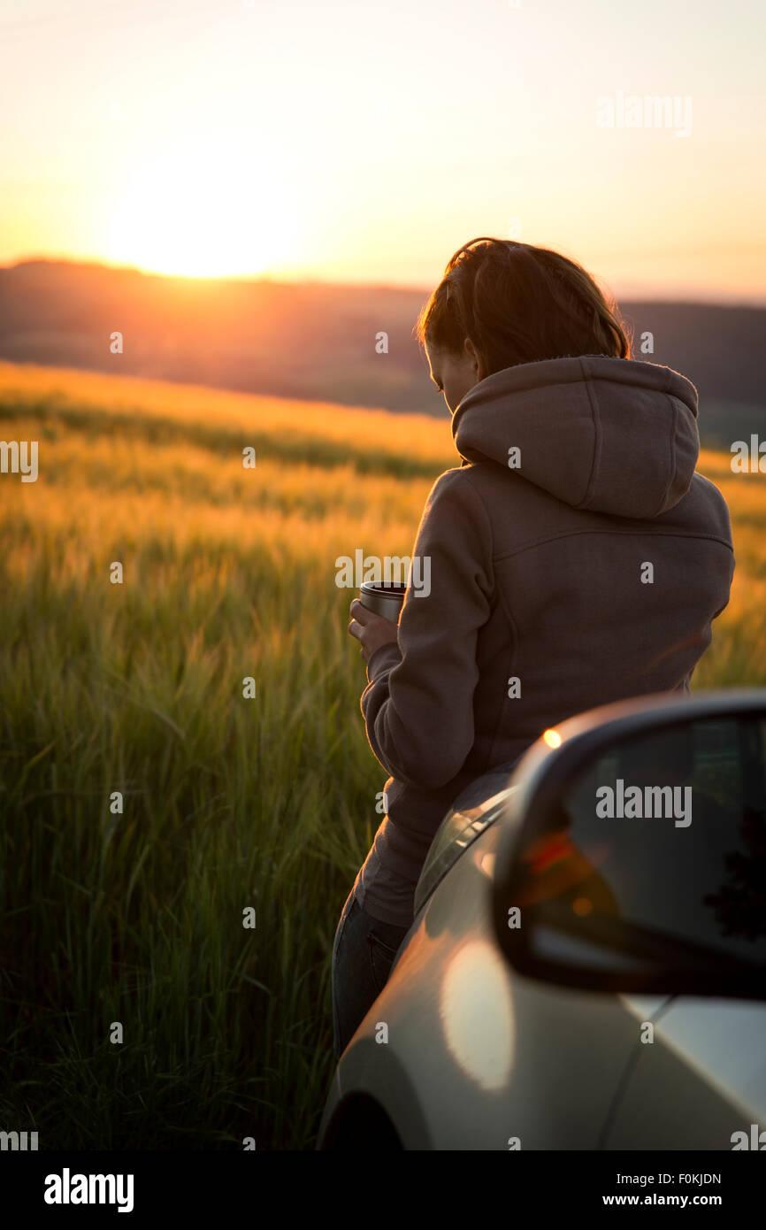 Deutschland, Frau stützte sich auf Auto vor einem Feld bei Sonnenaufgang Stockbild