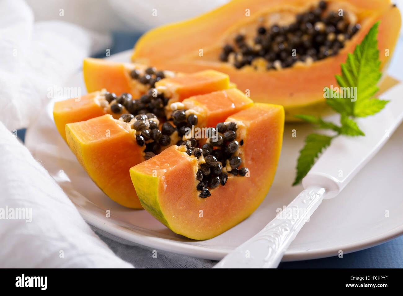 Schneiden von exotischen Früchten Papaya auf a blaue Tabelle Stockbild