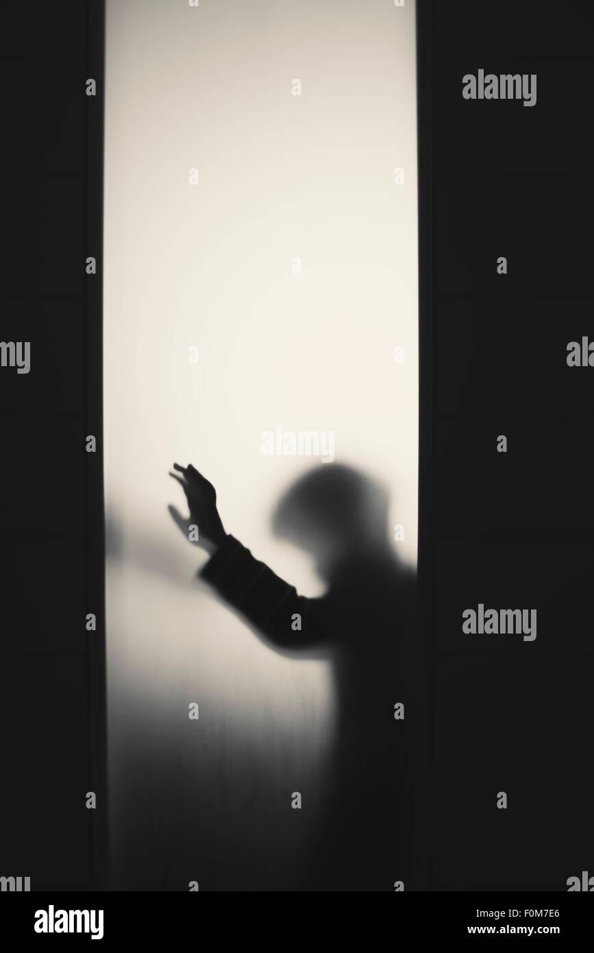 Silhouette eines kleinen Kindes mit erhobenem Arm. Konzeptbild von Kindheit Ängste, Missbrauch und Sicherheit Stockbild
