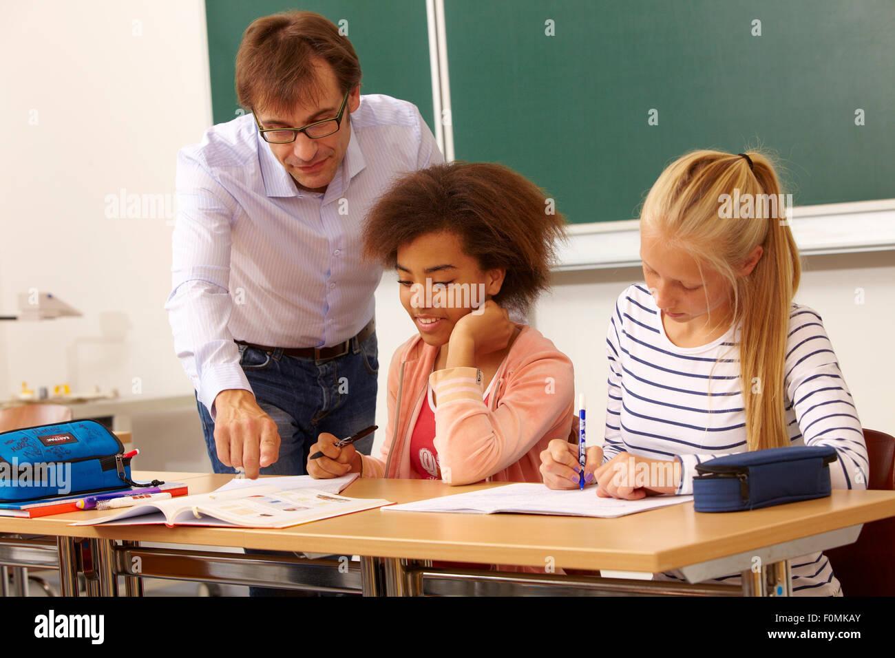 Lehrer hilft zwei Schülerinnen im Unterricht Stockfoto