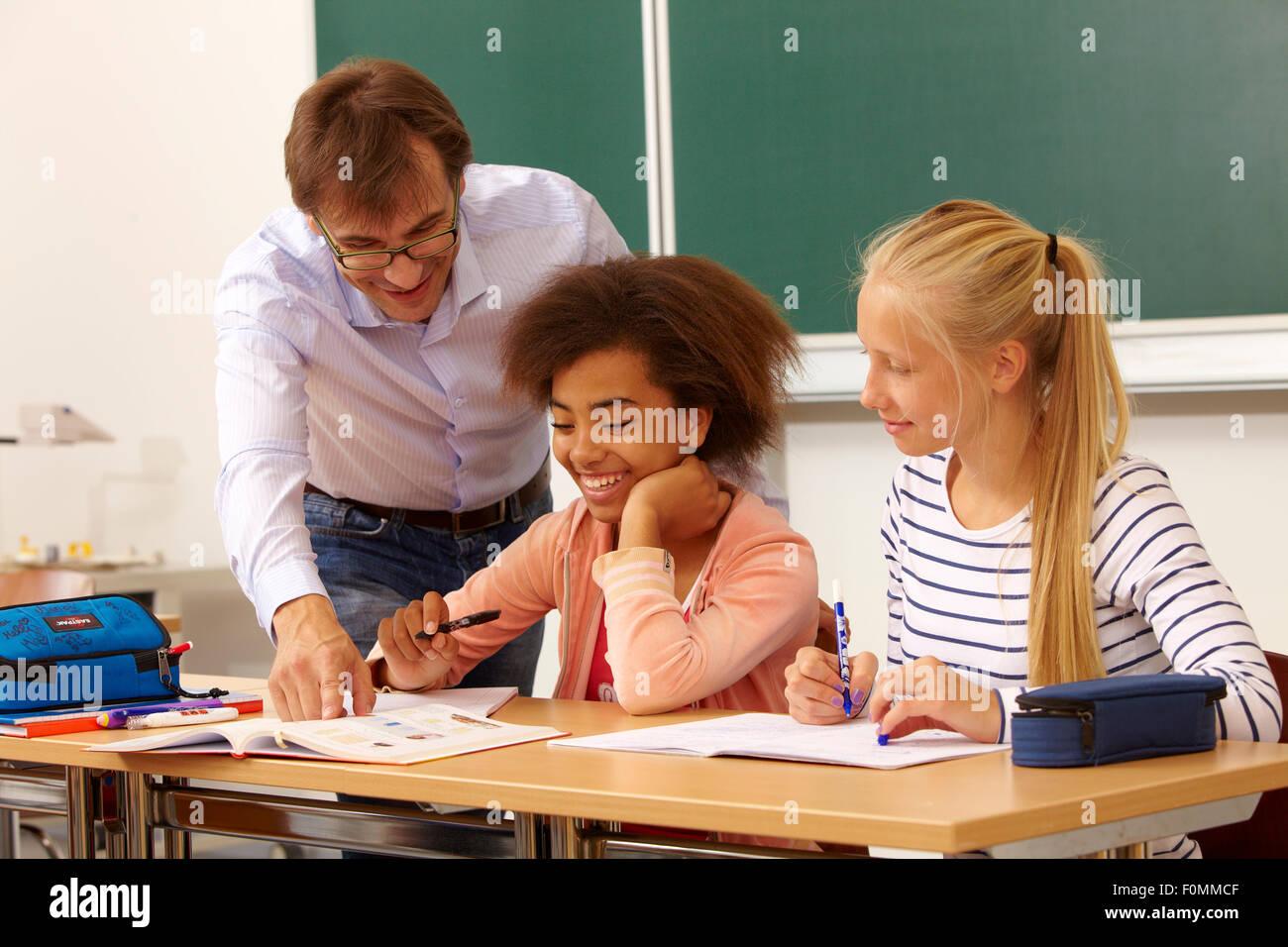 Lehrer hilft zwei Schülerinnen im Unterricht Stockbild