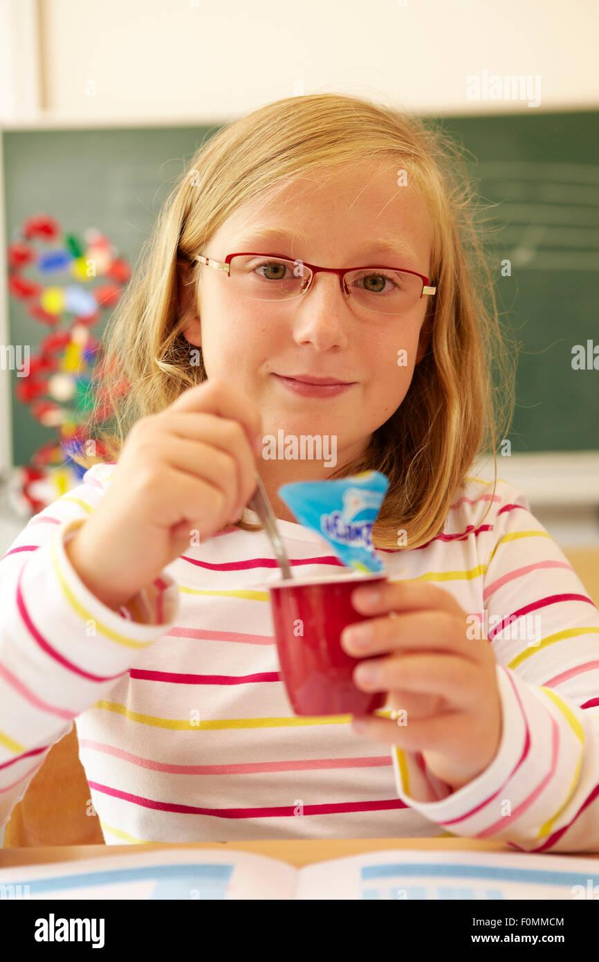Schulkind isst eine süße Frucht-Zubereitung Stockbild