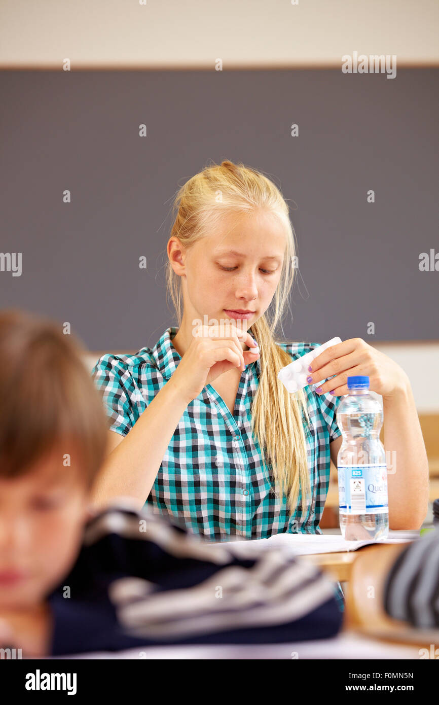 Mädchen in der Schule nimmt eine Pille Stockbild