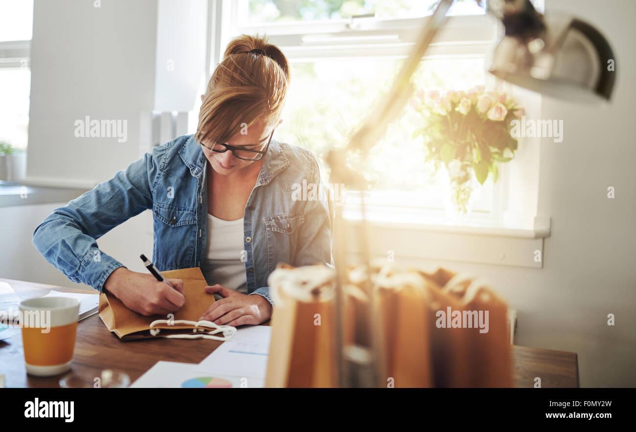 Junge Frau schreiben einige Notizen auf Papier Geschenktüte auf den Holztisch im Inneren des Hauses gegen die Stockbild