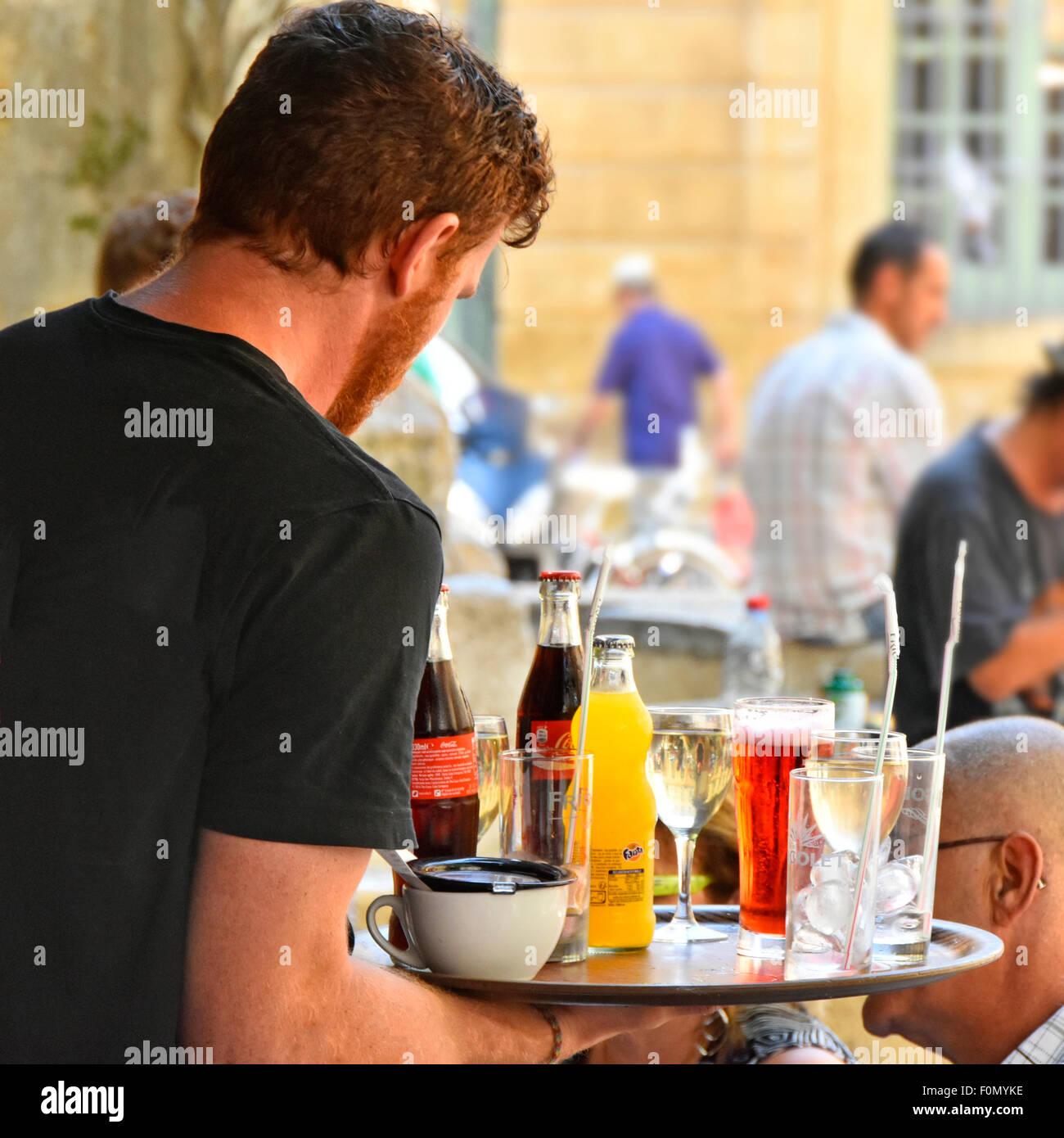 Französische Kellner trägt Fach voller Getränke an Kunden in bar im ...