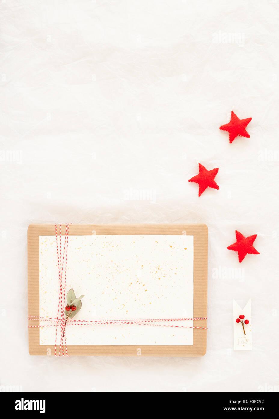 Geschenk verpackt mit braunem Papier, rote und weiße Bakers Bindfäden Weißbuch spritzte mit Goldfarbe Stockbild