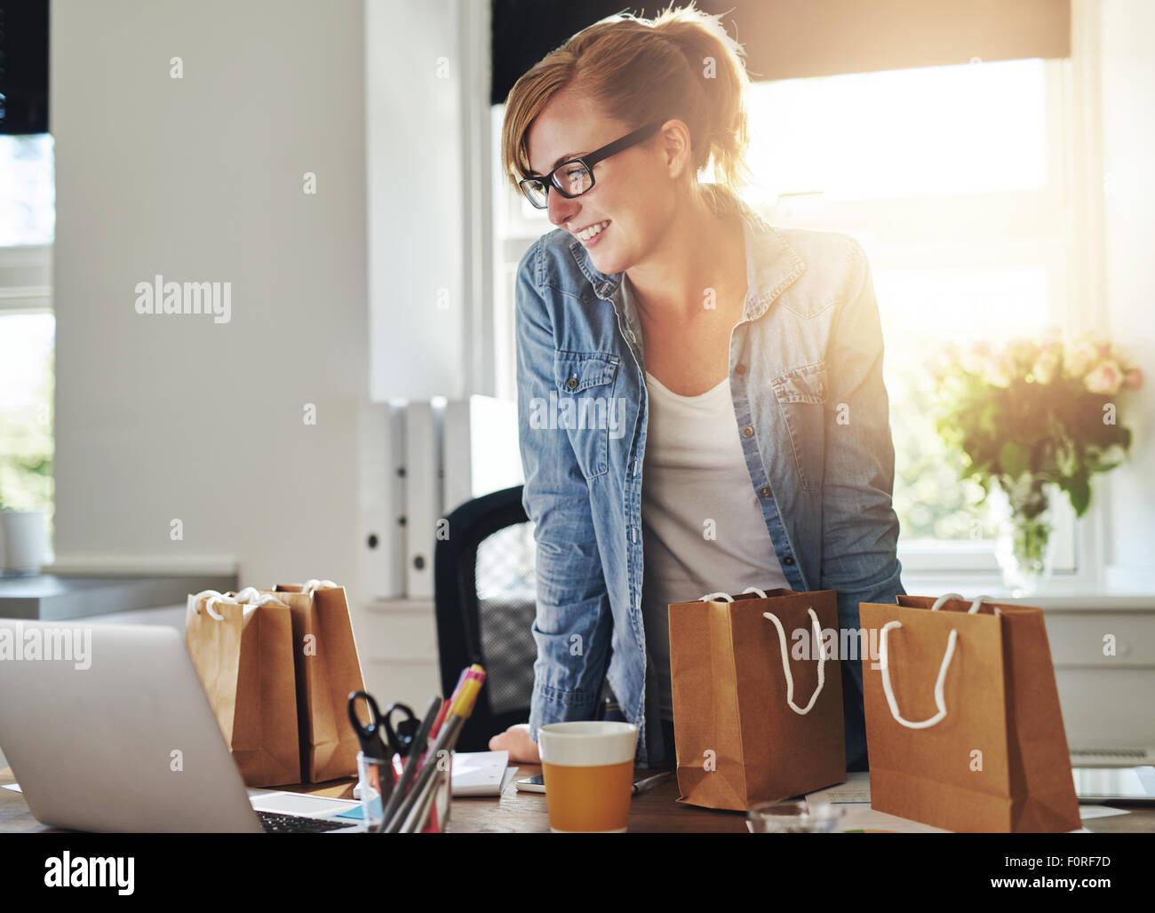 Glücklich Geschäftsfrau arbeiten im home-Office stehen auf ihrem Laptop-Computer, umgeben von Geschenk Stockbild
