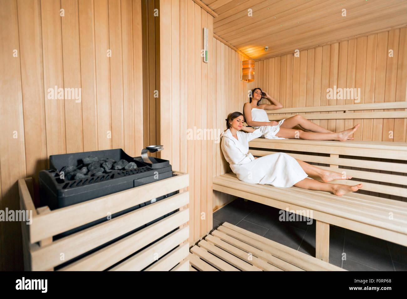 Saunaofen in eine gemütliche Sauna und Mädchen entspannen im Hintergrund Stockbild
