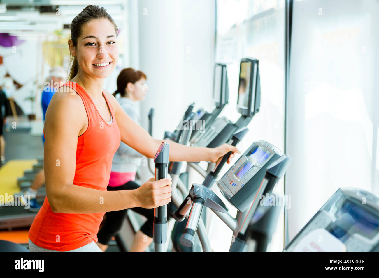 Junge passen Frau mit eine elliptische Trainer in einem Fitnesscenter und lächelnd Stockbild