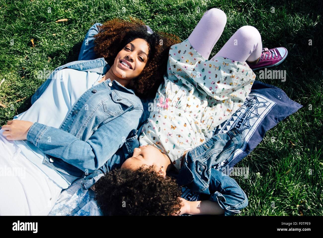 Erhöhte Ansicht von Mutter und Tochter liegen nebeneinander auf Rücken, Augen geschlossen Stockbild