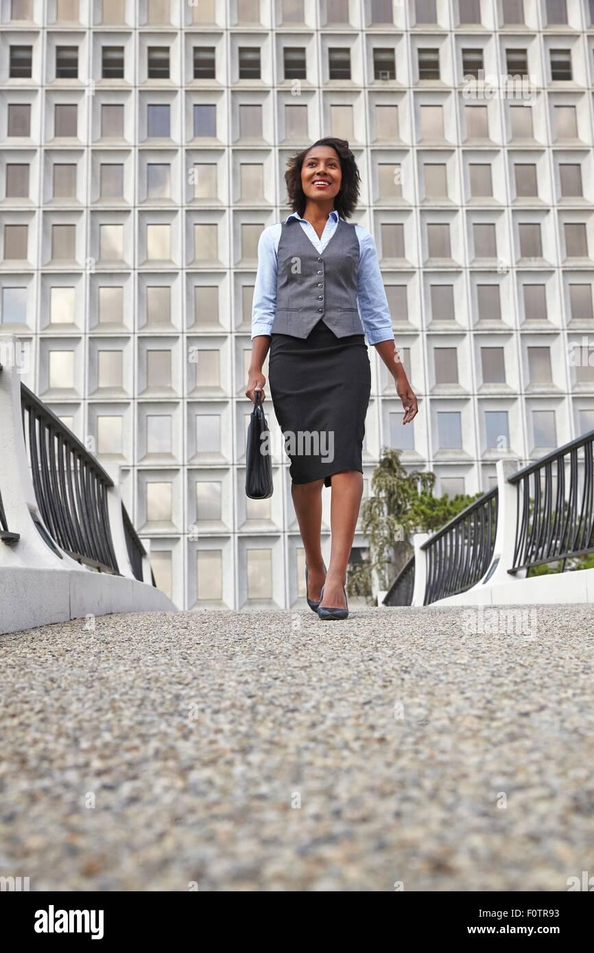 Niedrigen Winkel Vorderansicht der Geschäftsfrau Wandern, tragen Aktentasche, Lächeln, wegschauen Stockbild