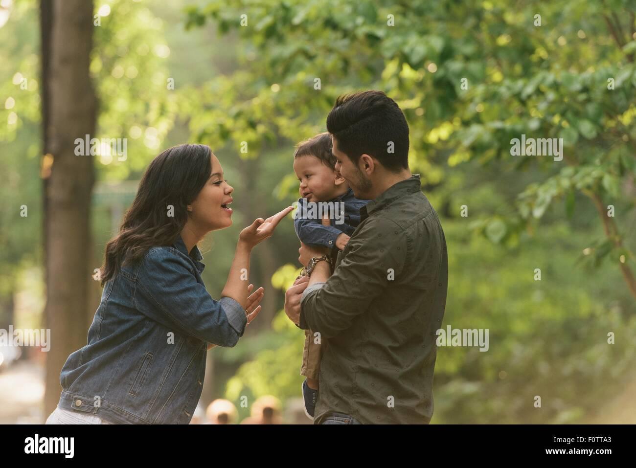 Seitenansicht von Mutter und Vater weht Kuss Baby jungen Stockbild