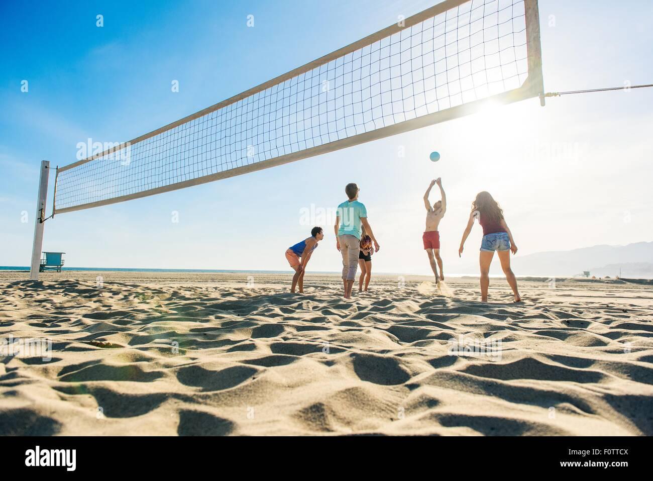 Gruppe von Freunden, die am Strand Volleyball spielen Stockbild