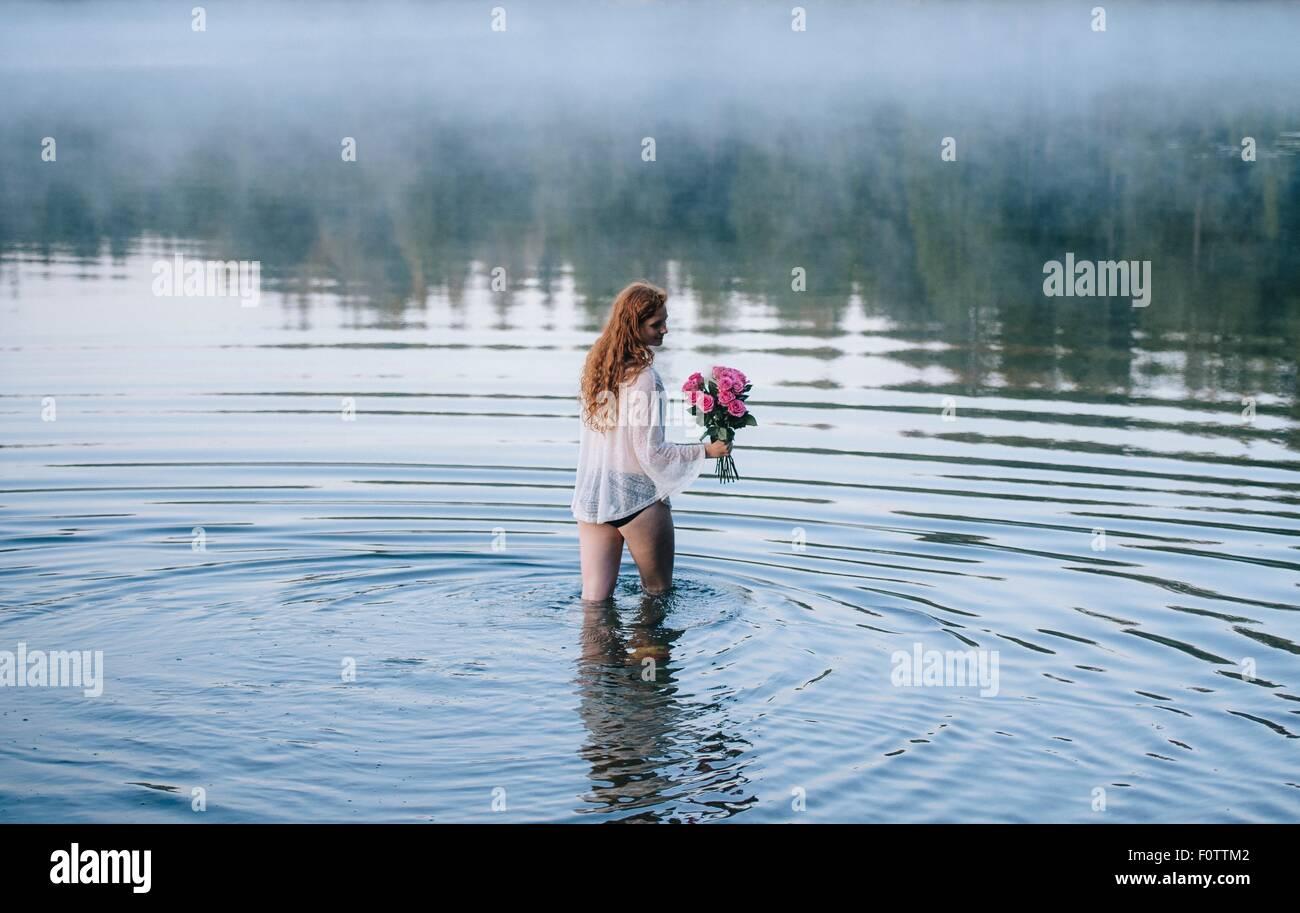 Rückansicht des jungen Frau waten im nebligen See hält Strauß rosa Rosen Stockfoto