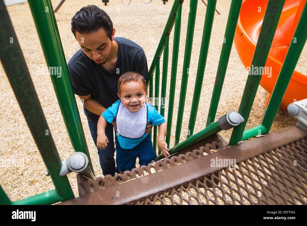 Junger Mann guiding Kleinkind Bruder Spielplatz Rutsche Treppe hinauf Stockbild