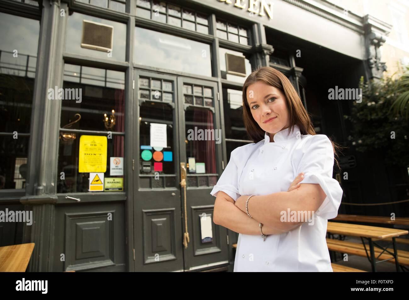 Mitte adult Koch stehen außerhalb der Arbeit verschränkten Armen Stockbild
