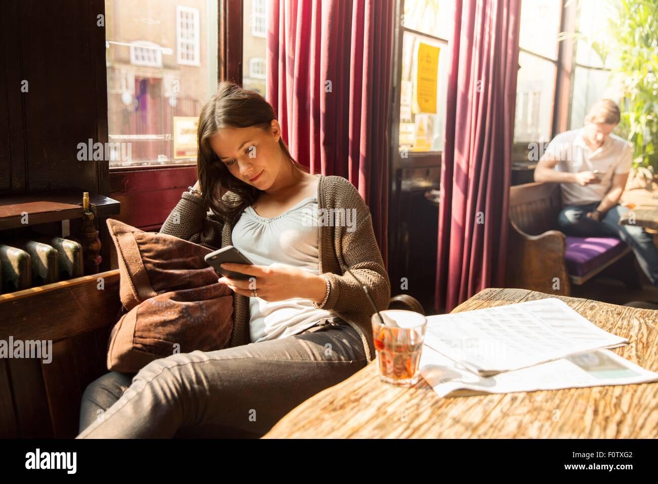 Mitte Erwachsene Frau sitzen Smartphone betrachten Stockfoto